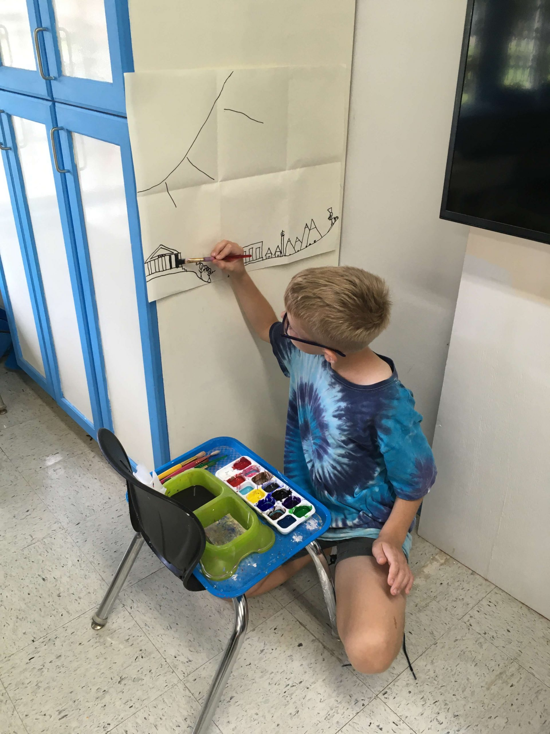 Gabe in art class working on a mural